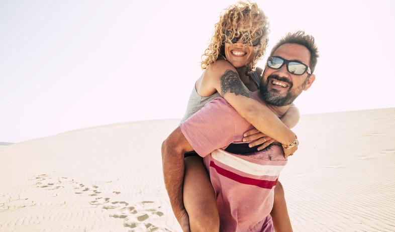 בני זוג מטיילים על דיונות ליד החוף במהלך חופשה (אילוסטרציה: simona pilolla, shutterstock)