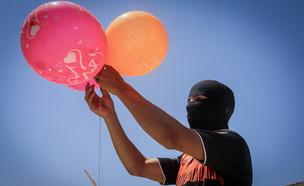תושב עזה מפריח בלוני תבערה לעבר ישראל (צילום: רחים קטיב, פלאש 90)
