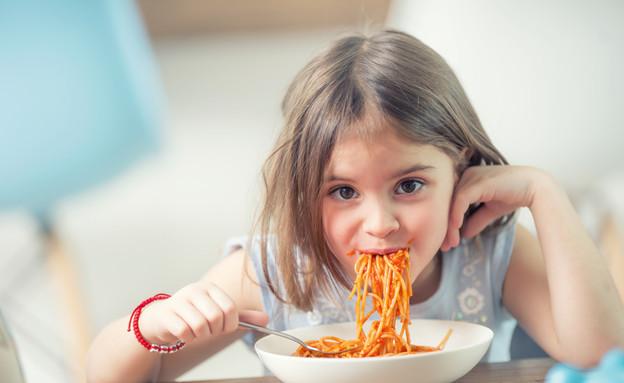ילדה אוכלת פסטה (צילום: shutterstock By Marian Weyo)