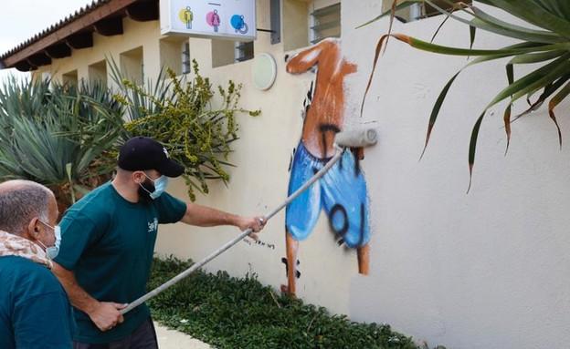 הסרת ציור הקיר בו נראים נערים מציצים למלתחות (צילום: רועי חבני)
