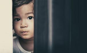 ילד מציץ מבעד לדלת ברזל (אילוסטרציה: Mama Belle and the kids, shutterstock)