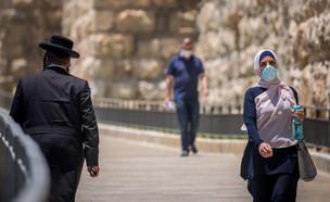 גבר חרדי ואישה ערביה עם מסיכת פנים הולכים ליד שער יפו בירושלים (צילום: יונתן סינדל, פלאש 90)