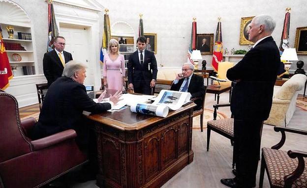 טראמפ כשוודוורד מולו, סגן הנשיא פנס מימינו ועל השולחן תמונה של קים