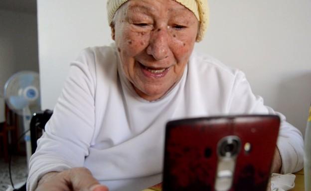 דינה שדה מדברת בפלאפון עם נכדיה