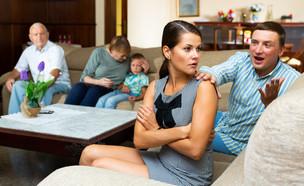 אישה צעירה עצבנית אחרי ריב עם בעלה מול ההורים (אילוסטרציה: Iakov Filimonov, Shutterstock)