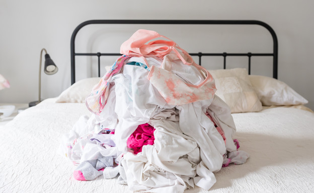 ערמת כביסה על מיטה (צילום: shutterstock / Natalie Board)