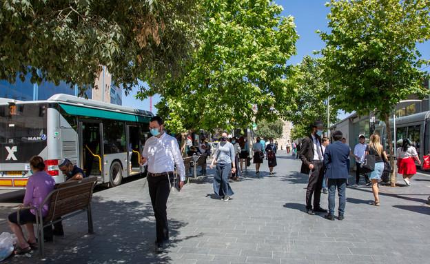 אנשים במסיכות ליד תחנת אוטובוס בירושלים (צילום: Alex Eidelman, shutterstock)