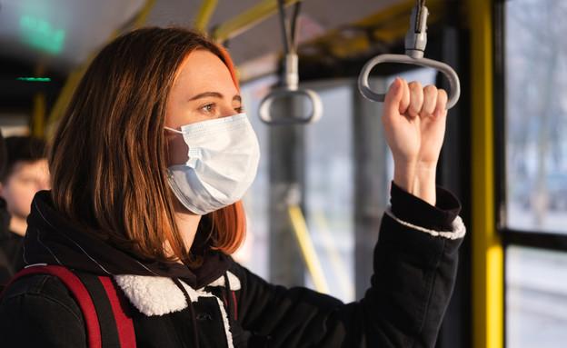 אישה עם מסכה באוטובוס (צילום:  Aleksey Boyko, shutterstock)