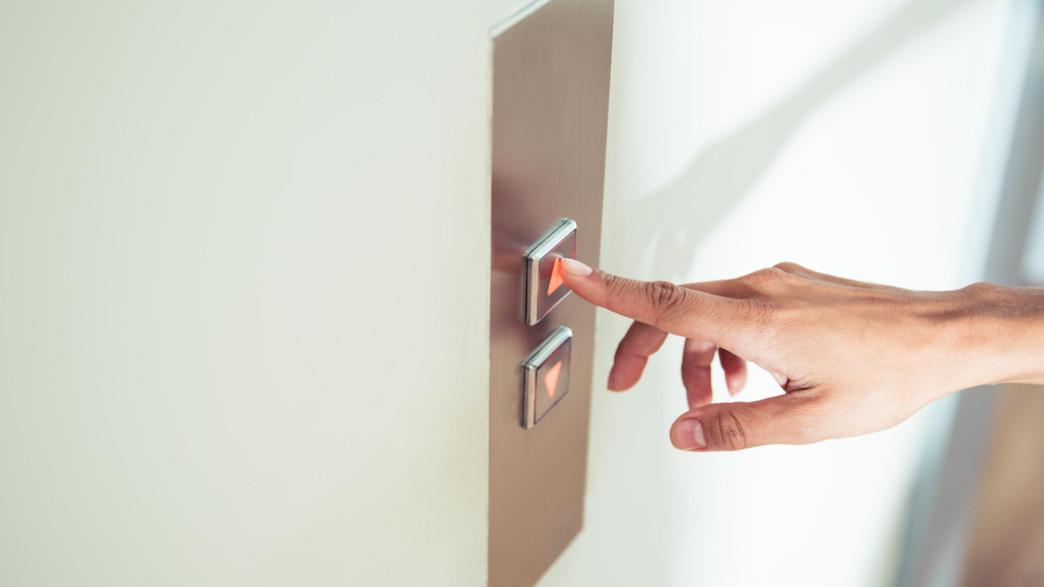 לוחץ על כפתור של מעלית (צילום: Dean Drobot, shutterstock)
