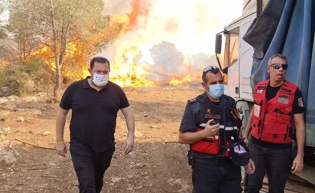 יוסי דגן, ראש המועצה האזורית שומרון, ברקע השרפה (צילום: וועדי הישובים מבוא דותן ומעוז צבי)