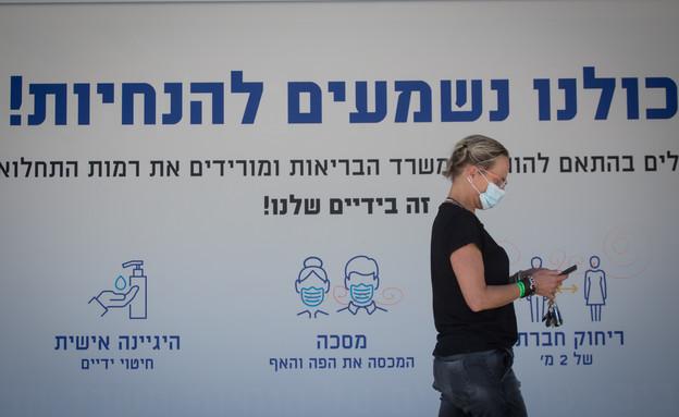 אישה עם מסכה על רקע הנחיות הקורונה (צילום: מרים אלסטר, פלאש 90)