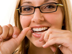 בחורה במשקפיים עושה חוט דנטלי (צילום: istockphoto)