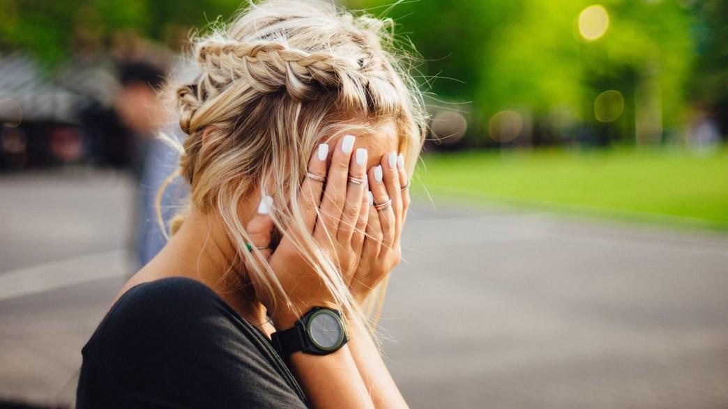 אישה מכסה את פניה בידיה (אילוסטרציה: abigail keenan, unsplash)