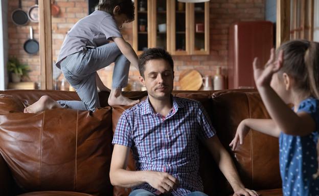 אבא מותש יושב על ספה בזמן שילדיו משתוללים (אילוסטרציה:  fizkes, shutterstock)