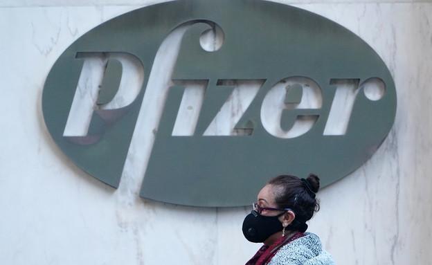 אישה עם מסכה חולפת ליד הבניין המרכזי של חברת פייזר (צילום: רויטרס)