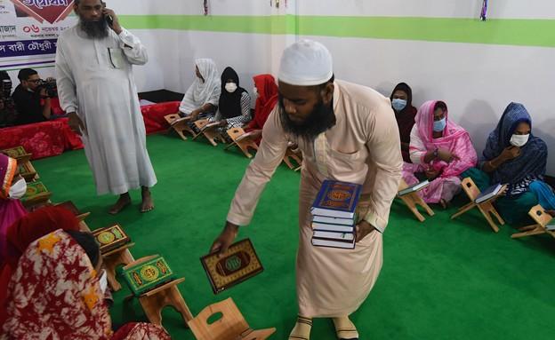 מורה מחלק ספרי קוראן לתלמידות הטרנסג'נדריות, בנגלד (צילום: MUNIR UZ ZAMAN/AFP, GettyImages)