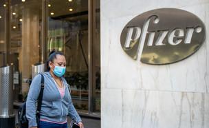 אישה עם מסכה חולפת ליד הבניין המרכזי של חברת פייזר (צילום: David Dee Delgado, getty images)