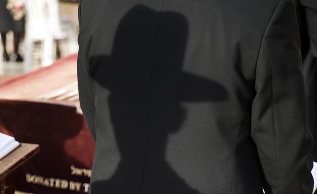 צל של חרדי על חליפה של מתפלל אחר (אילוסטרציה: elbud, shutterstock)
