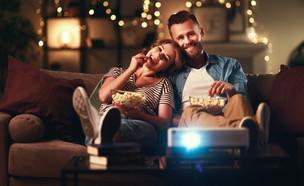 זוג צופה בסרט בבית באמצעות מקרן (צילום: Evgeny Atamanenko, shutterstock)