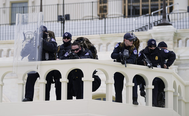 שוטרי הקפיטול מכוונים נשקים לכיוון המפגינים במטרה למנוע מהם להיכנס (צילום: AP)