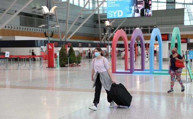 תושבים עוטים מסיכה בנמל התעופה הבינלאומי בסידני, אוסטרליה (צילום: שי פרנקו, רויטרס)