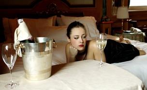 אישה יפה מחכה במיטה עם שמפניה (אילוסטרציה: shutterstock)