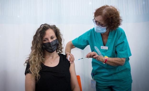 Un membre de l'équipe à Sheba reçoit la deuxième dose de vaccin (Photo: Miriam Elster, Flash 90)