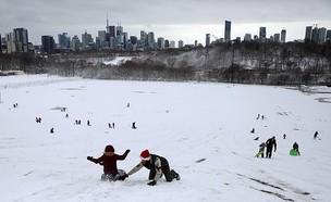 תושבי האזור משתעשעים בשלג שנערם בשטח המחנה (צילום: רויטרס)