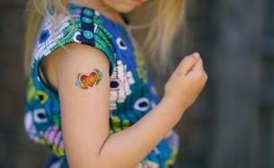 ילדה עם קעקוע של לב קומצת אגרוף (אילוסטרציה: Jeremy McKnight, unsplash)