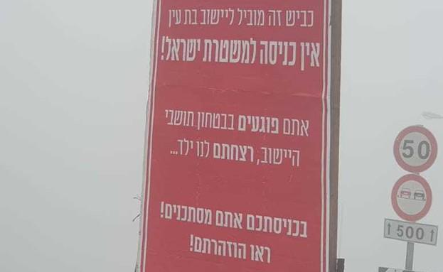 השלט שנתלה בכניסה ליישוב בו מתגוררת משפחת סנדק (צילום: דוברות המשטרה)