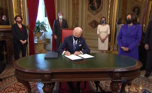 ג'ו ביידן חותם על המסמכים (עיבוד: רויטרס)