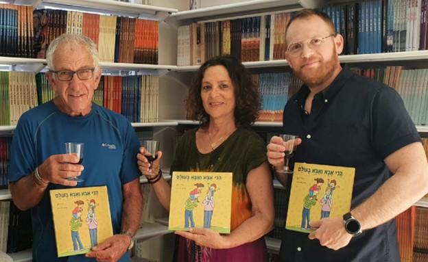 """ג'ודי דגן ובני משפחתה עם ספר הילדים """"הכי אבא ואבא בעולם"""" (צילום: פזית עמר, יחסי ציבור)"""