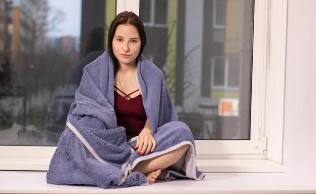 אישה יושבת על עדן החלון, עטופה בשמיכה (אילוסטרציה: oliavvvesna, shutterstock)