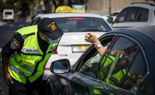 שוטר בודק כלי רכב במחסום זמני בירושלים בזמן הסגר, ספטמבר 2020 (צילום: יונתן סינדל, פלאש 90)