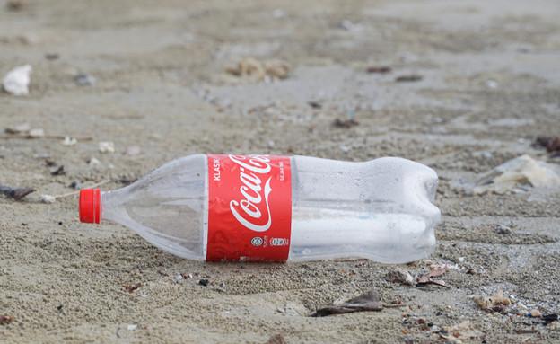 בקבוק קוקה קולה זרוק בחוף (צילום:  Fazly Marijal, shutterstock)