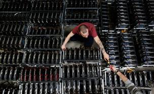 עובד במפעל כריית הביטקוין של החברה הסינית ביטמיין, איטליה (צילום: רויטרס)