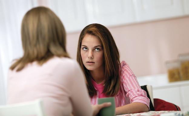 נערה בוורוד יושבת בפרצוף כועס מול אישה (צילום: jupiter images)