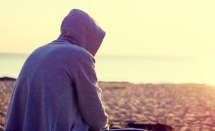 גבר יושב בחוף (צילום: Sabphoto, Shutterstock)