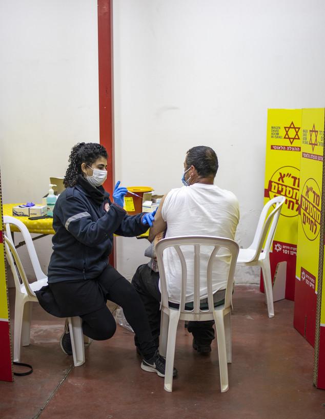 פלסטיני מקבל חיסון נגד קורונה באזור התעשייה ברקן (צילום: אריאל שליט ל-AP)