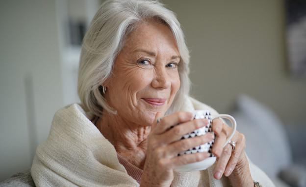 אישה מבוגרת שותה (צילום:  goodluz, shutterstock)