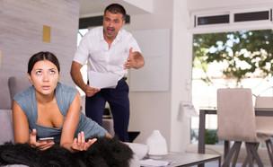 אישה מתוסכלת שוכבת על ספה בסלון וגבר צורח עליה (אילוסטרציה: shutterstock)