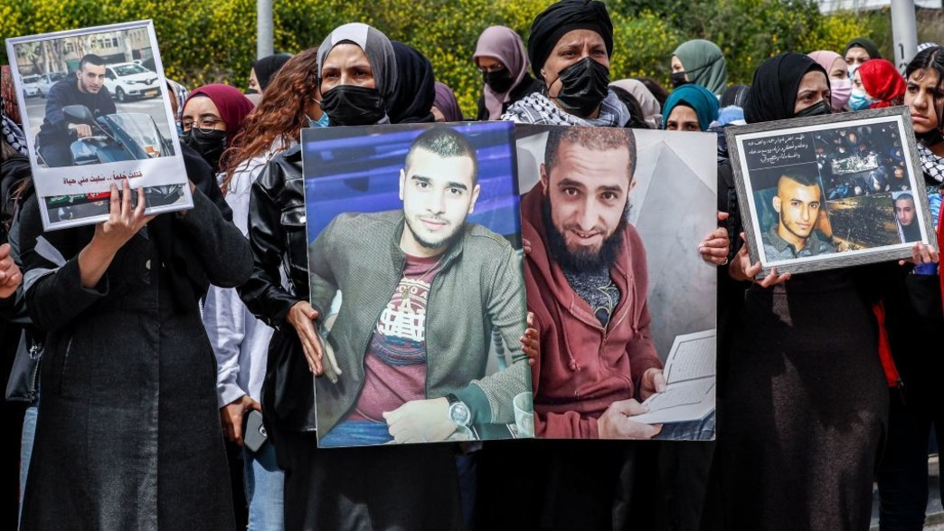 מפגינות באום אל פחם מחזיקות תמונות של נרצחים (צילום: AHMAD GHARABLI, AFP)