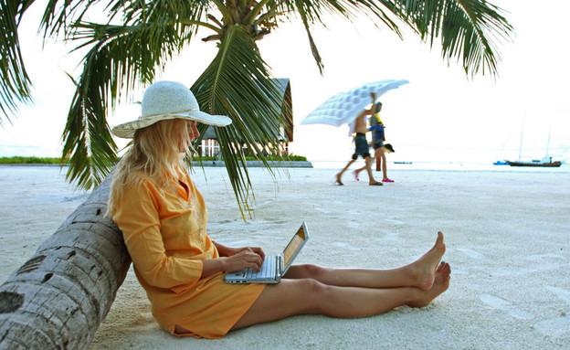 אישה עובדת עם לפטופ וטלפון סלולרי באתר נופש במלדיביים (צילום: EyesWideOpen, Getty Images)