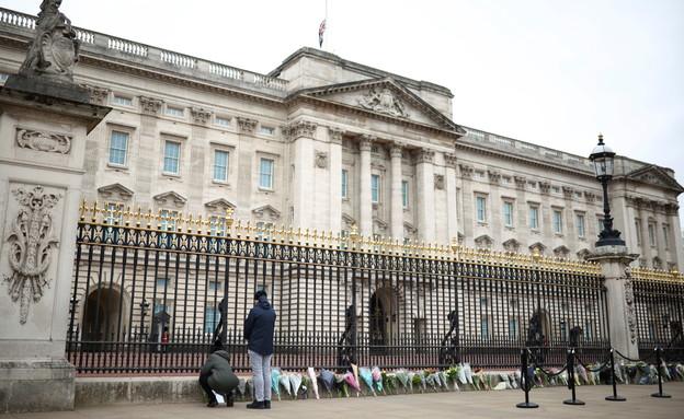מניחים פרחים בחזית ארמון באקינגהם לזכרו של הנסיך (צילום: רויטרס)