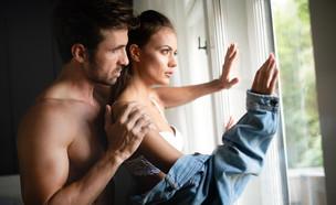 אישה וגבר עומדים ליד חלון (אילוסטרציה: NDAB Creativity, shutterstock)