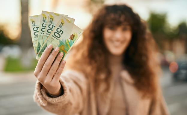צעירה מחייכת מחזיקה שטרות של שקלים (אילוסטרציה: Krakenimages.com, shutterstock)