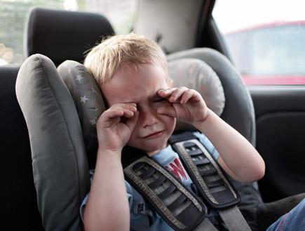 ילד בוכה במכונית (צילום: shutterstock By Maria Symchych)