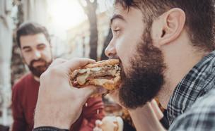 גבר אוכל המבורגר (צילום: zeljkodan, shutterstock)