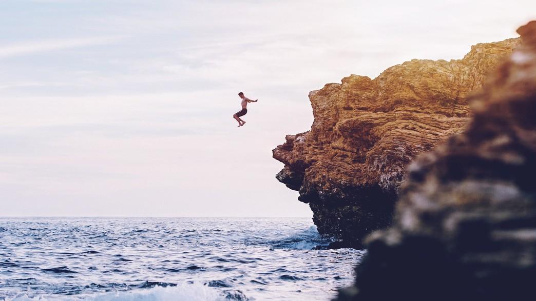 בחור קופץ מצוק (צילום: Austin Neill UNSPLASH)