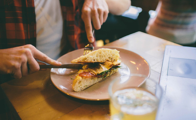 גבר אוכל במסעדה (צילום:  Estrada Anton, shutterstock)